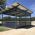 Large Square BBQ shelter with skillion roof and colorbond slatted panels for both the shelter sides and sun screening under roof