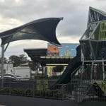 Customised shade structure with stingray shape suspended over children's play area from one corner post