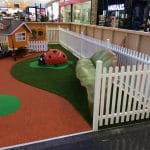 Children's play area inside shopping centre with white picket fence, rubber surfacing, lady bug sculpture, leaf seat and cubby house