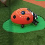 Large lady bug sculpture sitting on rubber wetpour pad surrounded by synthetic grass