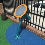 Outdoor musical equipment bright coloured drum in rubber wetpour in front of a black fence