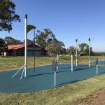 Outdoor fitness equipment, tall post with rope to climb up and angled cargo net for jumping on and hanging from