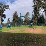 Outdoor fitness circuit for school aged children on hillside with synthetic grass
