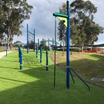 Outdoor fitness equipment in synthetic grass with tall post attached to climbing rope for children to climb up and ring bell
