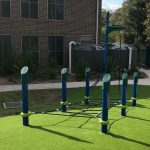 Outdoor fitness equipment in synthetic grass with horizontal cable net for children to step through