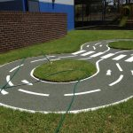 Trike track design in rubber wetpour surfacing with white line markings for the road and pedestrian crossing
