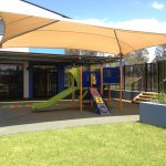Pre School playground with Playshaper unit under shade structure with green slide and abc climber