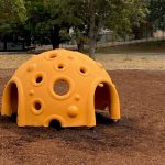 Plastic dome play item for children's playground with side entry points and a number of viewing holes for children to see through
