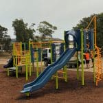 Playsense play unit in primary school with long blue slide and bright green and orange play pieces in bark mulch