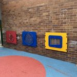 Wall mounted sensory play panels, yellow chimes, blue marble panel and red ball maze panel