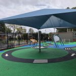 Outdoor special needs play area with rubber bike track graphics, shade structure and rotating net