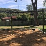 Single Post swing set with a strap seat and a half bucket seat for infants in a bark mulch play area