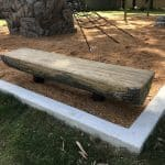 GFRC Log Bench half log like bench made out of concrete set in bark mulch area