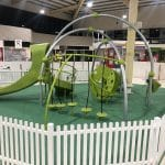 Shopping Centre playground surrounded by white picket fence with large steel arches and bright green play items