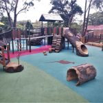 Accessible playground with ramps leading to large log like climbing pieces and slides made out of concrete