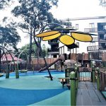 Ramp leading to deck over sandpit with large yellow flower shaped shade structure over the sandpit