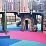 GFRC Tree Trunk Cubby under children's playground with bright coloured rubber wetpour surfacing