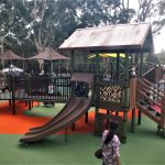 Children's playground in bush setting with large tin roof with rusted corrugated iron with a double curved slide