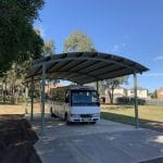 Large Curved roof shelter over a concrete slab with mini bus underneath the shelter
