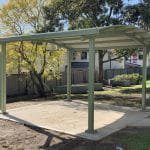 Pale Eucalypt Frame Shelter with a curved roof installed over a concrete slab