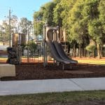 playground equipment with high double slide in a tan like colour leading into a bark mulch pit at the end