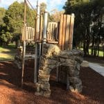 playground equipment with rock like formation arch entry that bends around platform