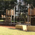 playground equipment with large vertical central climbing net natural looking rocks and sandstone edging