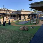 outdoor play area with synthetic grass and rubber wetpour track with natural timber features