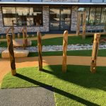 timber totem poles in synthetic grass in front of a dry creek bed