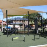 outdoor fitness ninja circuit with green rubber surfacing and a cream coloured shade sail over the top
