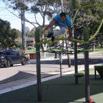 man jumping off a high cargo net frame in an outdoor fitness circuit