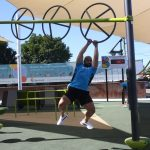 man hanging from wheel on a fitness course with three large wheels