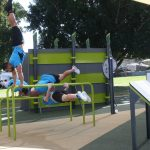 multiple fitness men on a parallel bar performing gymnastic positions
