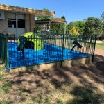 Play area with blue rubber flooring timber retaining wall and playground equipment