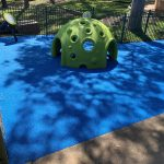 Bright green dome in playground with blue rubber flooring