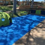 Outdoor play area blue rubber floor with bright green equipment