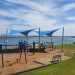 Two blue shade sails over a children's plagyround area in front of the coast line