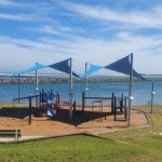 Two blue shade sails over a playground unit with the coastline in the background