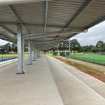 Metal Skillion shelter overlooking hockey field with tiered concrete steps underneath