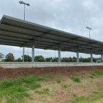 Metal Skillion spectator shelter installed on top of hill over multi level tiered concrete slab