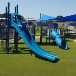 high blue double slide with tube slide on synthetic grass