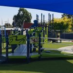 accessible playground with ramps leading up to large hex deck areas with sensory play panels