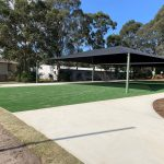 synthetic grass area under large blue shade structure with concrete pathways