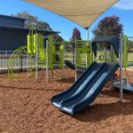 Playground under shade in bark mulch with blue double slide