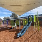 Playground under shade in bark with high blue single plastic slide and bright green climbing equipment