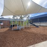 Playsense playground structure under shade structure in bark mulch with metallic silver posts and blue and bright green equipment
