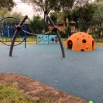 Play area with orange dome spider web climber and spin bar