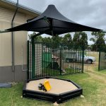 sandpit with single post umbrella shade over