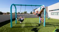 Arch frame swing with little girls swinging high on the swing