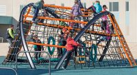 High steel framed climber with cable net webbing with children climbing over the structure